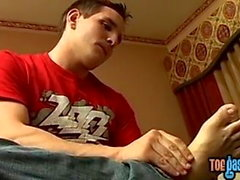 Hung jock caresses his tired soles before jerking off