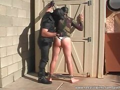Spanking guy on leash outdoors
